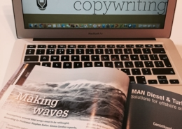 Magazine with Making Waves article in front of laptop with Bydand Copywriting logo